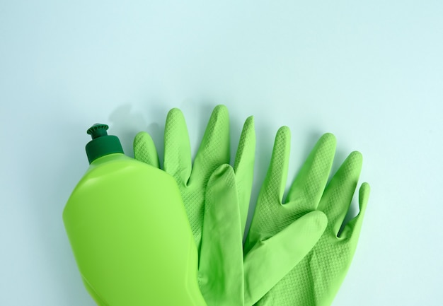 Зеленые резиновые перчатки для очистки и очищающей жидкости в пластиковой бутылке на синем фоне, плоская планировка, вид сверху