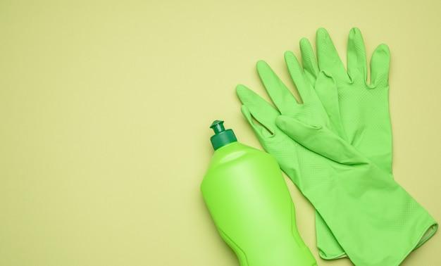 Зеленые резиновые перчатки для очистки и очищающей жидкости в пластиковой бутылке на зеленом фоне, плоская планировка, копия пространства