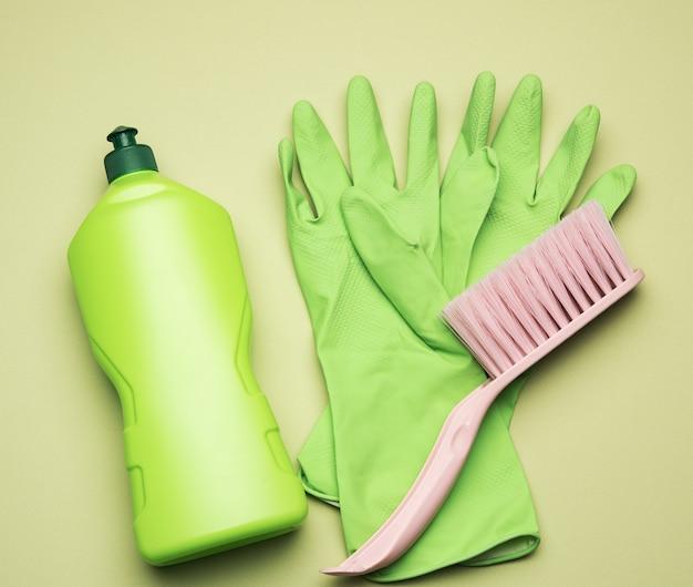 Зеленые резиновые перчатки для чистки, розовые щетки и чистящая жидкость в пластиковой бутылке на зеленом фоне