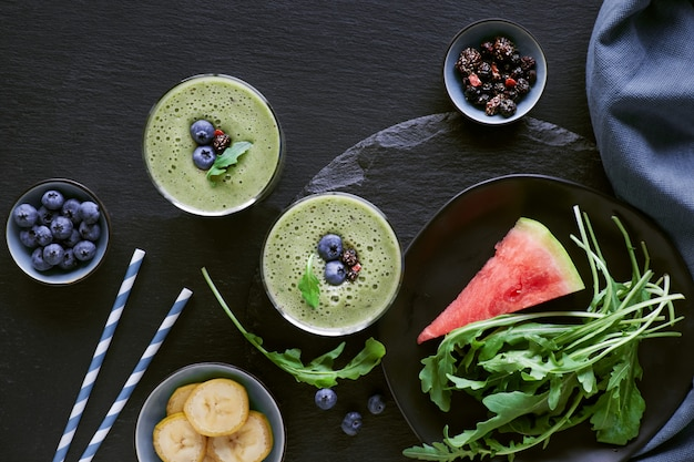 Green rucola, banana and watermelon smoothie in glass jars on dark slate ,