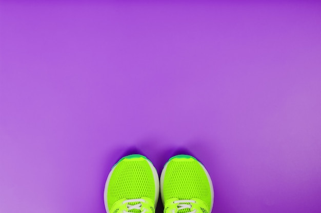 Green running shoes on a purple background. top view, free space