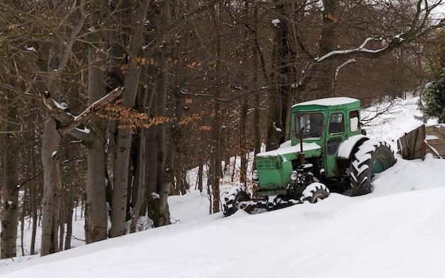 雪の降る天気で緑の素朴な古いトラクター