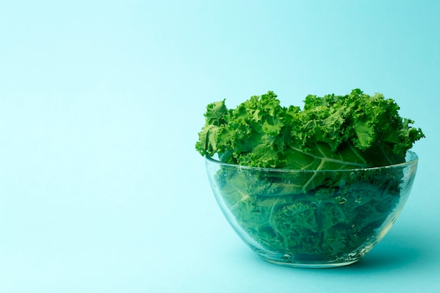 Зеленый салат в стеклянной миске на синем