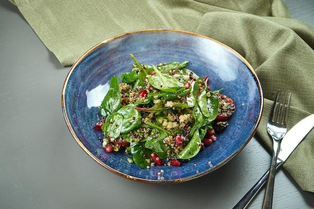 木製のテーブルの青いプレートにキノアとザクロの種子とグリーンサラダ(ほうれん草)。食欲をそそるダイエット食品。ベジタリアン