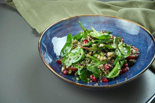 木製のテーブルの青いプレートにキノアとザクロの種子とグリーンサラダ(ほうれん草)。クローズアップ、スペースをコピーします。ベジタリアン。