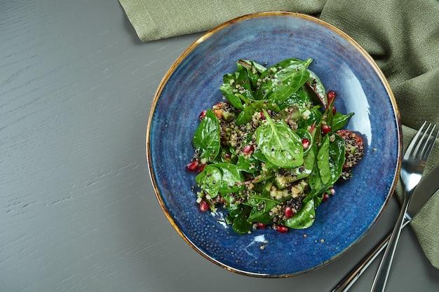 木製のテーブルの青いプレートにキノアとザクロの種子とグリーンサラダ(ほうれん草)。コピースペースとフラットが横たわっていた。ベジタリアン。上面図