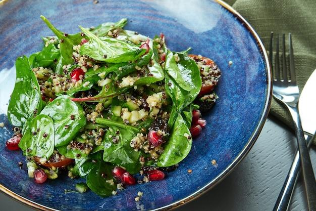木製のテーブルの青いプレートにキノアとザクロの種子とグリーンサラダ(ほうれん草)。セレクティブフォーカス。ベジタリアン。