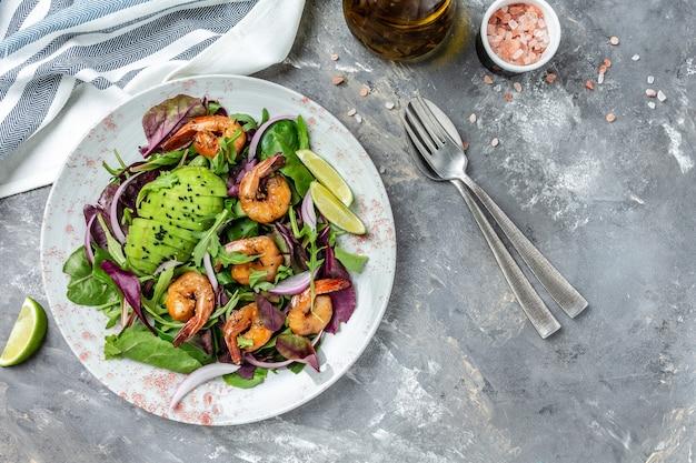Зеленый салат с авокадо и салатом из креветок. концепция морепродуктов. вкусный овощной микс из листьев, креветки на гриле. вкусный завтрак или закуска на сером фоне, вид сверху.