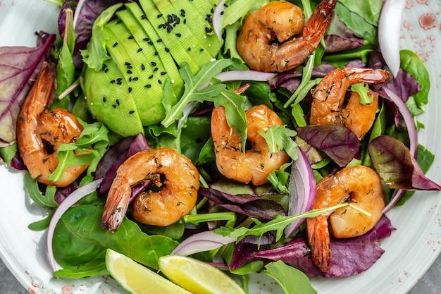 Зеленый салат с авокадо и салатом из креветок. концепция морепродуктов. вкусный овощной микс из листьев, креветки на гриле. здоровая пища. чистая еда. предпосылка рецепта еды. закройте вверх.
