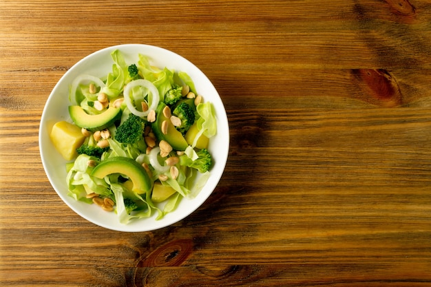 Green salad with avocado, cucumber, broccoli, potatoes and peanuts on white restaurant plate. healthy organic vegan salat with sliced alligator pear or avocado pear top view with copy space