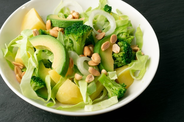 Green salad with avocado, cucumber, broccoli, potatoes and peanuts on white restaurant plate. healthy organic vegan salat with sliced alligator pear or avocado pear