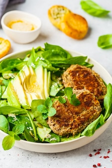 Green salad with avocado, cucumber and lentil cutlet in white plate.