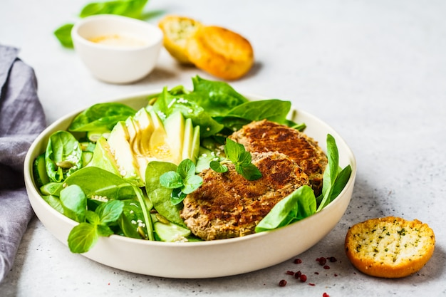 Green salad with avocado, cucumber and lentil patties in white plate.