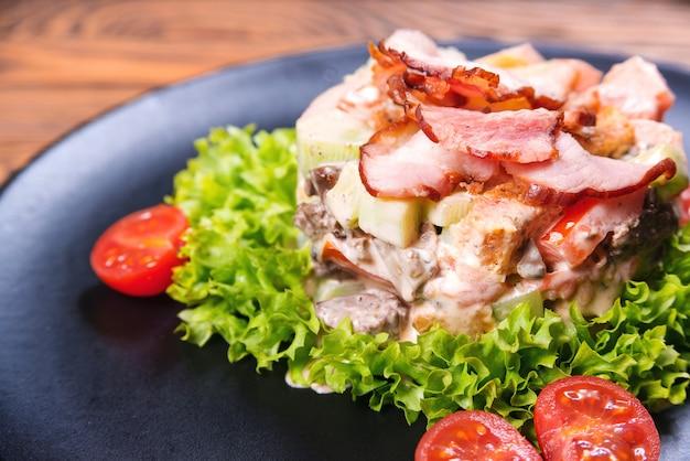 ベーコン、トマト、クルトン、レタスのクローズアップとグリーンサラダ。シーザーサラダの背景。健康的なダイエット食品の概念。