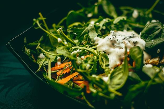 건강식, 음식 배달 서비스 및 주문 온라인 개념을위한 바질과 화이트 마늘 크림 소스가 들어간 그린 샐러드