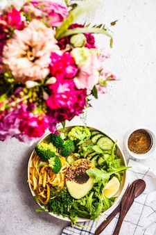 Green salad with broccoli, zucchini pasta, avocado and dressing.