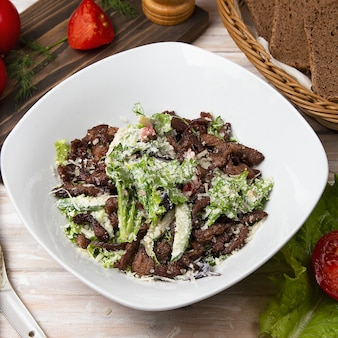 Green salad with brown mushrooms, chopped meat, lettuce and parmesan.