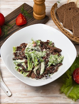Green salad with brown mushrooms, chopped meat, lettuce and parmesan
