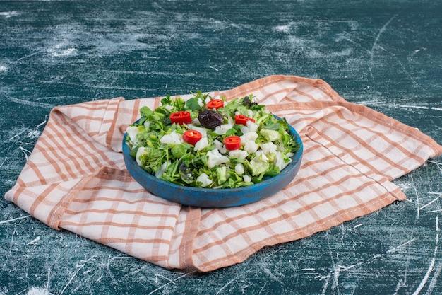 Зеленый салат с рубленым салатом на синей поверхности.