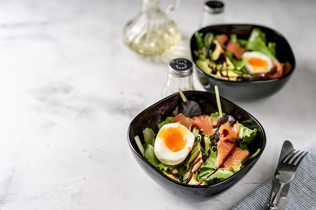 Green salad with egg and salmon for breakfast