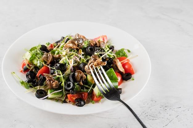흰색 바탕에 escargot 포도 달팽이와 그린 샐러드. 프랑스 미식가 요리.