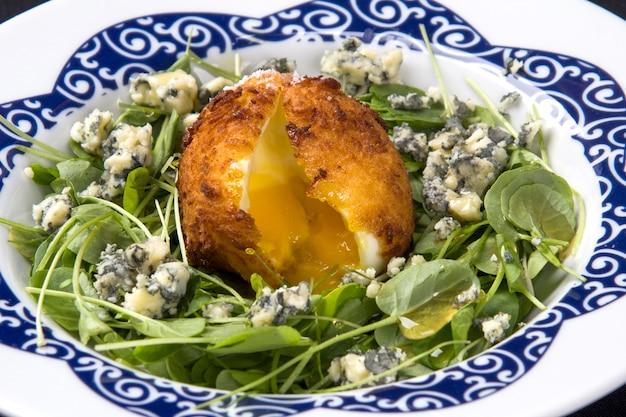 달걀 프라이와 하얀 접시에 치즈와 그린 샐러드.