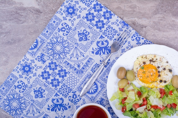 Green salad with fried egg and a cup of tea