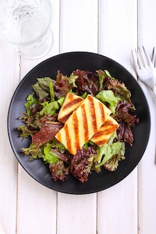 Green salad with fried halloumi cheese on a black plate