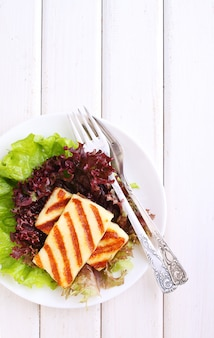 Green salad with fried halloumi cheese in a white plate on a white wooden background
