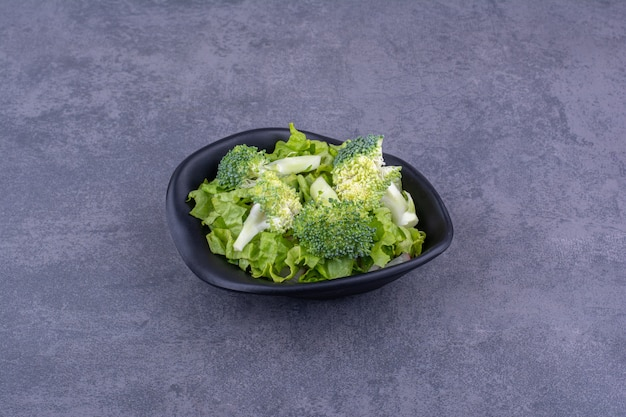 Зеленый салат с зеленью и специями в керамической тарелке
