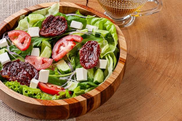 Зеленый салат с листьями салата, рукколой, огурцом, сыром и вялеными помидорами.