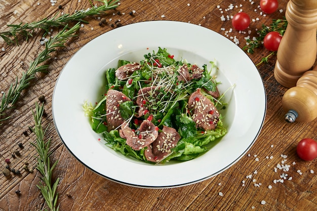 Зеленый салат с листьями салата, жареный телячий язык в белой миске на деревянной поверхности в композиции со специями