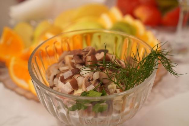 Зеленый салат с грибами в красивой тарелке.