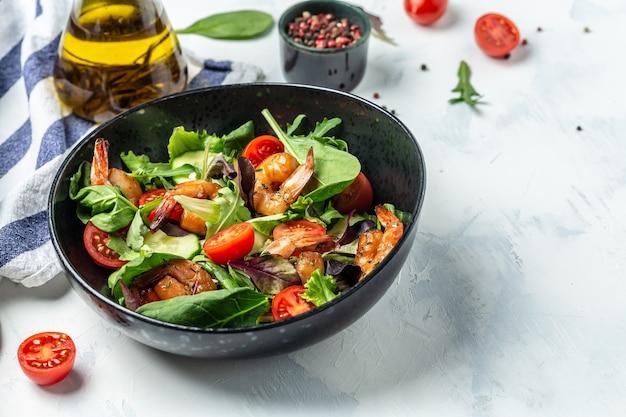 Зеленый салат с копчеными креветками, помидорами черри, огурцом и смешанными листьями. концепция морепродуктов. вкусный завтрак или закуска на светлом фоне, вид сверху.