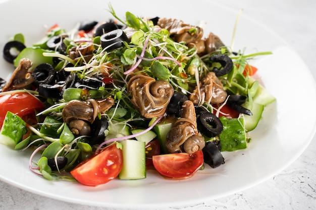 흰색 바탕에 달팽이와 그린 샐러드입니다. 프랑스 미식가 요리.