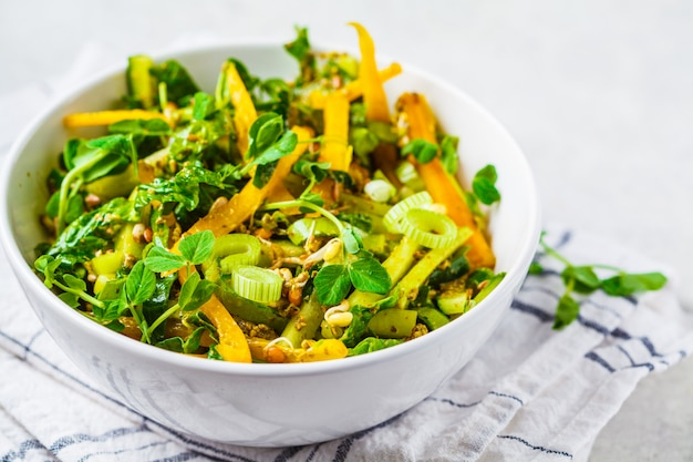 Green salad with spinach, pepper, cucumber, pesto sauce and sprouts in white bowl.
