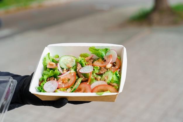 송아지 고기와 야채를 곁들인 그린 샐러드. 검역소에서 마스크와 검은 색 의료용 장갑으로 안전 배송. 에코 열 상자에 샐러드.