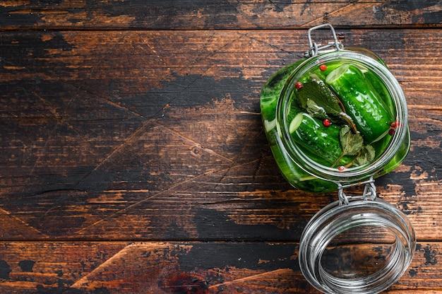 유리 항아리에 녹색 소금에 절인 오이. 어두운 나무 테이블. 평면도.