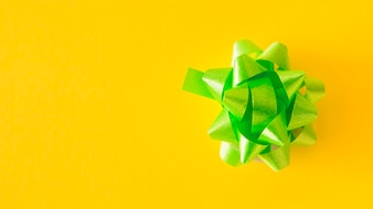 Green satin ribbon bow on yellow background