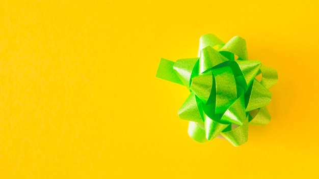 Green satin ribbon bow on yellow background