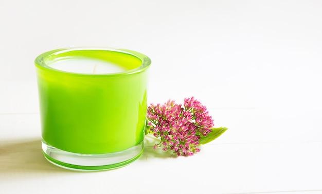 흰색 배경에 양치류와 천연 향기가 있는 녹색 향초. 아로마 테라피, 휴식, 바디 케어, 하모니. 복사 공간