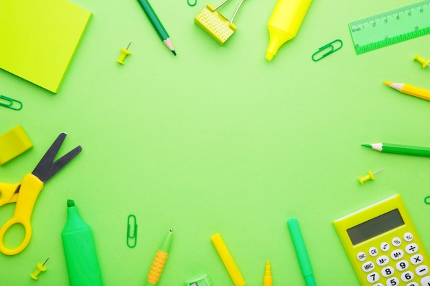 Green school accessories on light green background. back to school concept, minimalism
