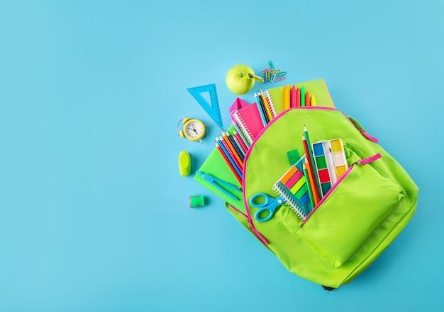 Green school bag full of school supplies on blue