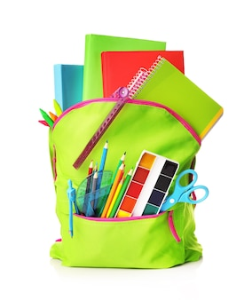 Green school bag full of school supplies isolated on white
