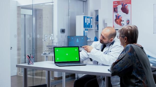 현대 민간 병원에서 의사의 그린 스크린 상담. 앱 또는 광고에 대한 크로마 키 키잉을 제거할 준비가 된 모형 모형 격리 배경