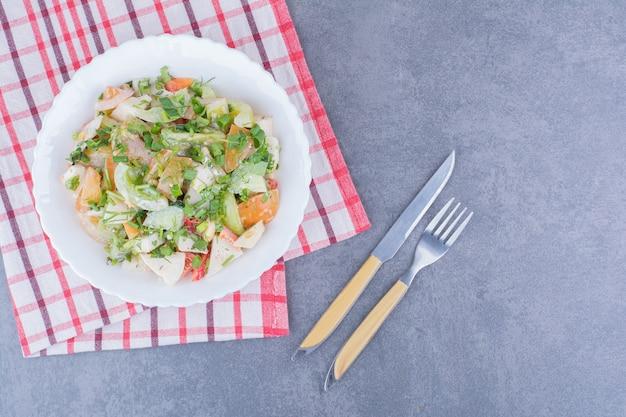 Insalata verde di stagione con verdure tritate e tritate in un piatto da portata