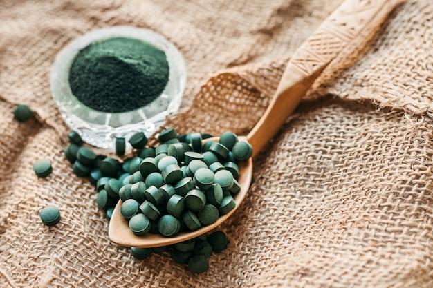 Зеленые водоросли спирулина в таблетках и порошке на фоне мешковины. растительный белок. копировать пространство