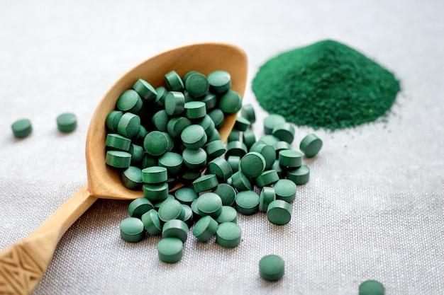 黄麻布の背景に錠剤と粉末の緑の海藻スピルリナ。植物性タンパク質