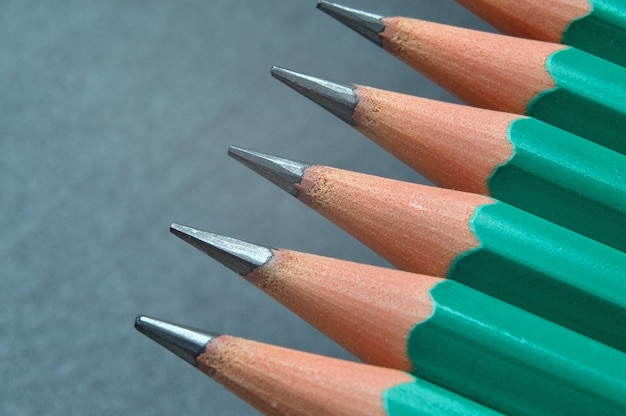 Green sharpened wooden pencils with black lead on a dark textured background. close-up.