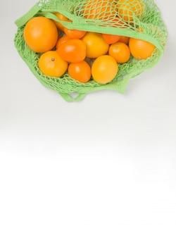 Зеленая корзина с оранжевыми фруктами и овощами